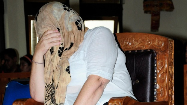 Lindsay Sandiford covers her face as she sits in a courtroom and listens to the judge