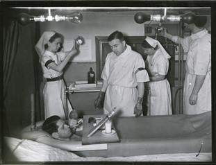 A burns patient enjoys a cigarette while in a saline bath while medical staff work in the background.
