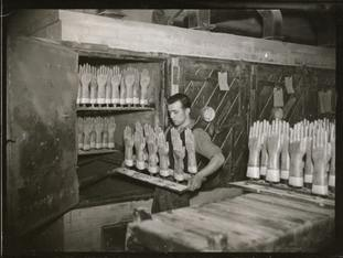 A man puts rubber gloves on moulds into an oven in a factory producing surgical gloves.