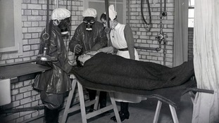 Nurses in protective clothing practice gas decontamination of a patient at Addenbrooke's Hospital in Cambridge in 1941.