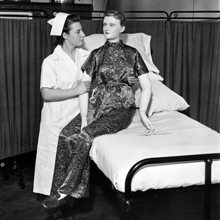 A student nurse uses a jointed-model to practice getting a patient out of bed in 1941.