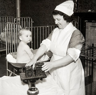A nurse weighs a baby on a set of balance scales in 1941.