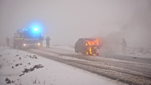 Fire fighters attend the car fire in Devon