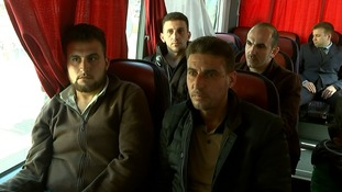 Syrians from Douma arrive on a bus to give evidence in The Hague.