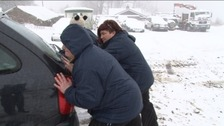 Carers pushing car out of snow