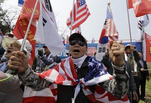 The historic meeting drew protesters in South Korea who shouted slogans and burnt flags