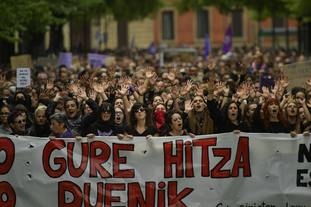 """Women hold up a sign reading in basque """"our word""""."""