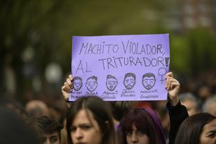 """A sign painted with the faces of """"La Manada"""" or Pack Leader, reading, """"Male violator to the crusher"""""""