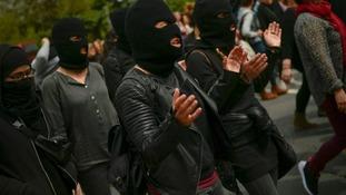 Masked women shout slogans in Pamplona.