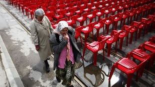 Women walk past some of the red chairs ahead of the official start of events for the 20th anniversary