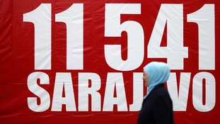 A woman walks near a banner with the number 11,541, to symbolise the red chairs