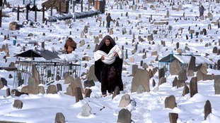 An Afghan woman walks through a snow covered graveyard in Kabul, 04 January 2006.