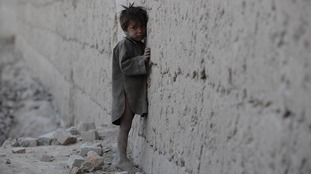 An Afghan boy leans against a wall as he cries on the outskirts of Kabul on October 4, 2011.