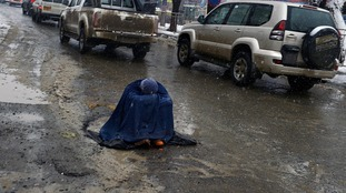 An Afghan woman begs for alms as she sits on a slush-filled road as snow falls in Kabul on February 4, 2013.