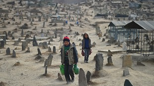 Afghan children who work as water vendors search for customers at the Kart-e-Sakhi cemetery in Kabul on January 12, 2015.