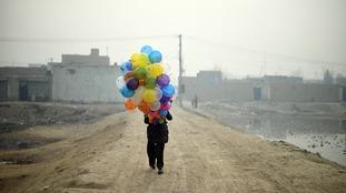 Afghan balloon vendor Arash, 19, waits for customers as he walks through a neighbourhood in Kabul on January 12, 2015.