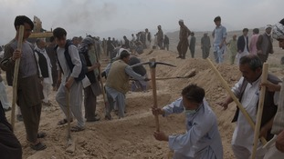 Afghan men dig graves for victims of a twin suicide attack, in Kabul on July 24, 2016.