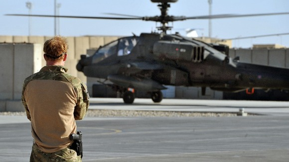 Harry watches the return from a mission of an Apache Helicopter