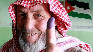 A man shows his ink-stained finger after voting at a polling station in Amman