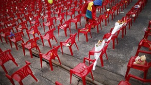 A child places a flower on a small chair symbolizing children killed