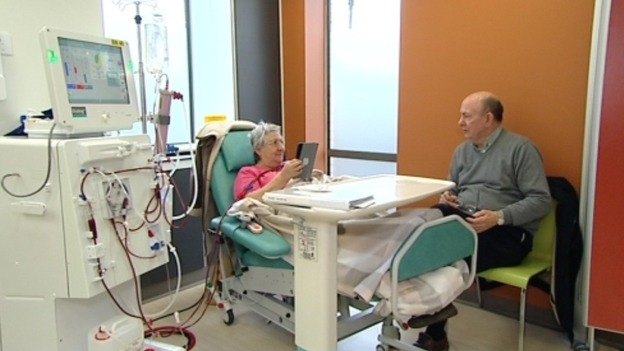 Woman in hospital bed talking to visitor