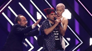 British Eurovision entry SuRie rushed by stage invader