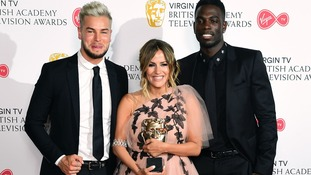 Caroline Flack with the award and Love Island participants Chris Hughes and Marcel Somerville in the press room at the BAFTA TV Awards.