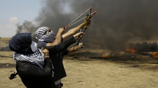 Palestinian protestors trade slingshot stones with live bullets and tear gas from Israeli troops at the Gaza Strip's border with Israel.