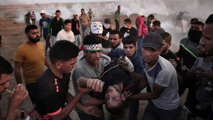 Palestinian protesters carry an injured man during a protest at the Gaza Strip's border with Israel.