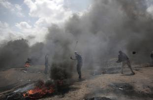 Palestinian protesters hurl stones at Israeli troops during a protest on the border. (AP)