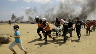 Palestinian protesters carry an injured man who was shot by Israeli troops.