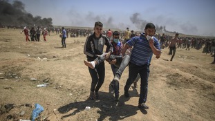 Palestinian protesters carry injured man during clashes with Israeli troops near the Gaza-Israel border, east of Gaza City