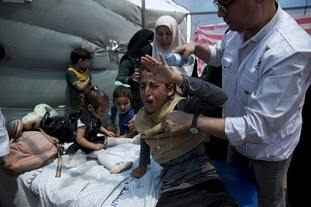Medics treat Palestinian children suffering from tear gas inhalation.