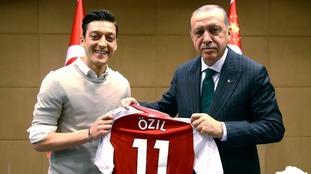 Mesut Ozil offers Turkish president Recep Tayyip Erdogan an Arsenal jersey.