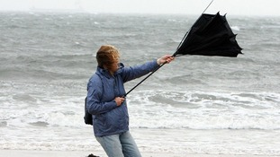 A woman struggles with her umbrella as high winds hit Tynemouth Beach, near Newcastle