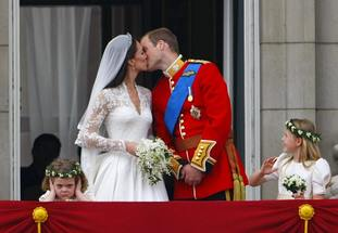 Prince William and his wife Kate Middleton kiss on the balcony as Grace van Cutsem covers her ears.