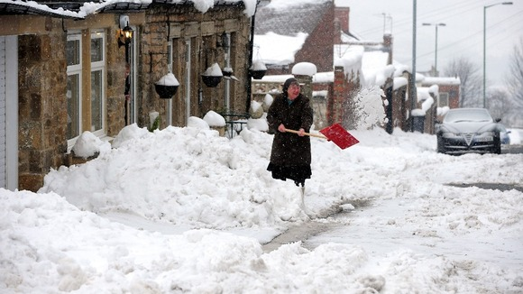 A woman digs her way out of snow in Tanfield County, Durham