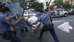 Anti-riot policemen use batons on a protester in Manila, Philippines
