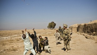 U.S. soldiers throw sweets to children in Afghanistan