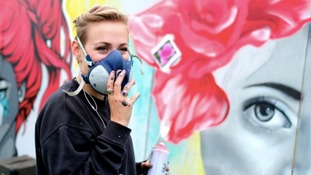 Artist with mask on and spray can in hand