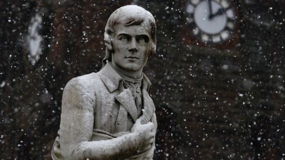 Snow falls onto a statue of Scotland's national poet, Robert Burns, in Dumfries