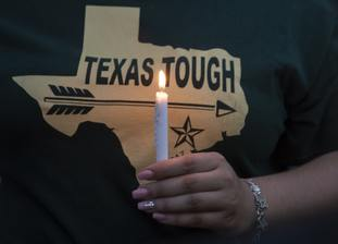 A woman wearing a Texas t-shirt holds a lighted candle during a vigil