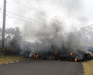 Lava crosses the road at Pohoiki Road near Pahoa, Hawaii.