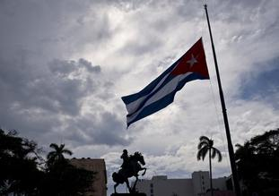 A Cuban flag is seen flying at half-mast near a statue of national hero Jose Marti