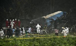 Rescue teams search through the wreckage site of a Boeing 737 that plummeted into a field