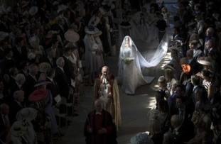 Meghan walks down the aisle lit by shafts of light.