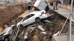 The gigantic hole dragged in three vehicles including a minivan.