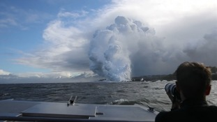A 'laze' cloud rises from the ocean as lava flow meets water.
