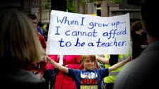 A boy holds up a banner saying: When i grow up I cannot afford to be a teacher&#x27;