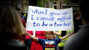 A boy holds up a banner saying: When i grow up I cannot afford to be a teacher'